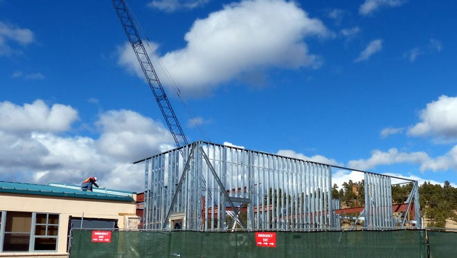 While a worker kneels on the roof, a steel frame  skeleton goes up at the front of Sierra Vista Primary.