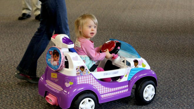 Ellie Stafford, 2, drives a modified toy car at Willamette Education Service District in Salem on Wednesday, June 3, 2015, in Salem, Ore. Sam Logan, with Oregon State University, taught a workshop to staff members at WESD to modify the cars to help children with disabilities gain independent mobility.