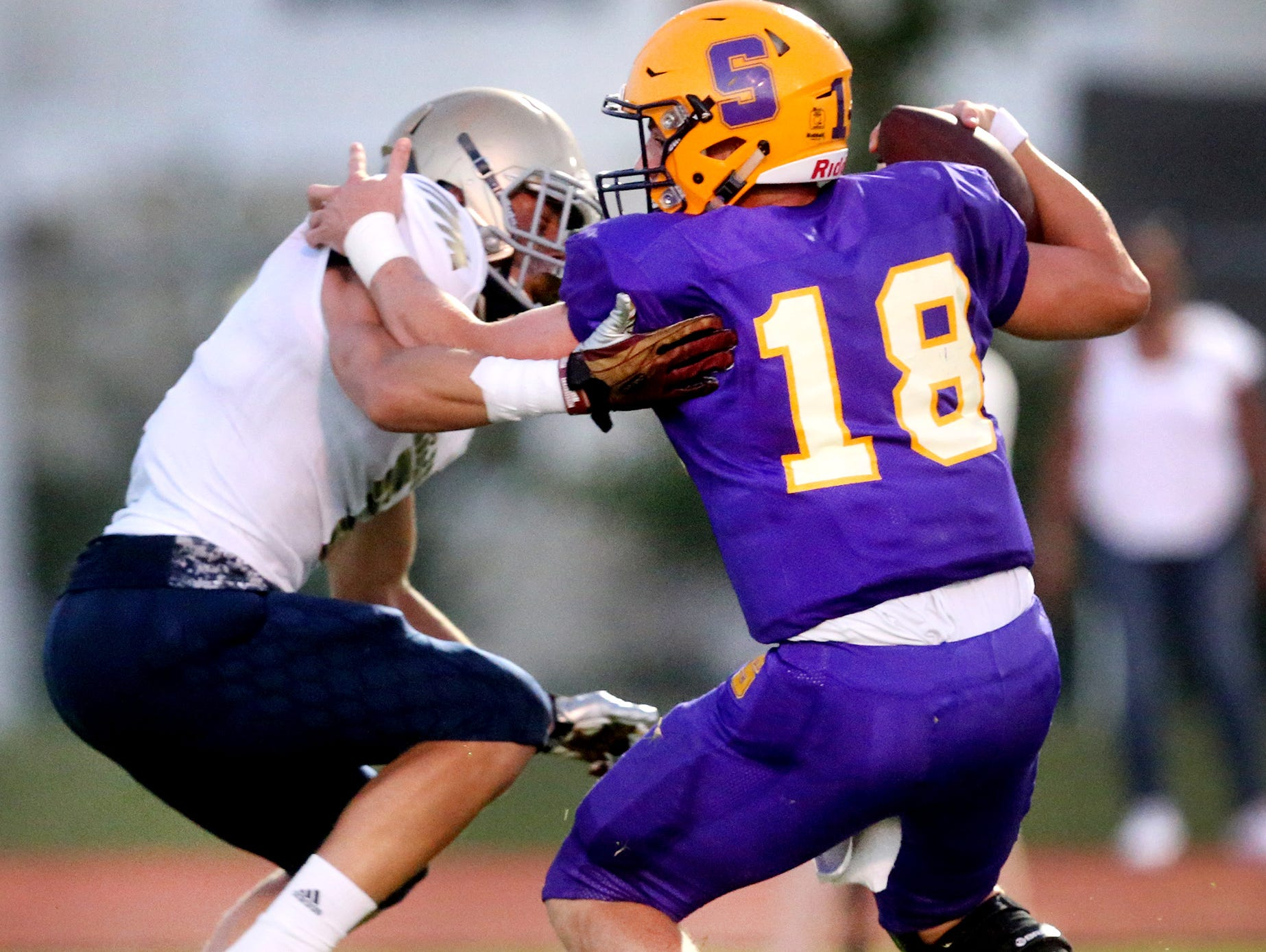 Smyrna's quarterback John Turner (18) tries to run the ball as Independence's Landon Guidry (7) sacks him on Friday, Sept. 9, 2016, at Smyrna.