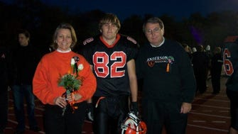 The author and staple of the Anderson High School football bench (middle) pictured with parents Bob Sr. and Jennifer at the AHS senior game in 2003. Courtesy of the Strickley family archive AKA an IBM Aptiva.