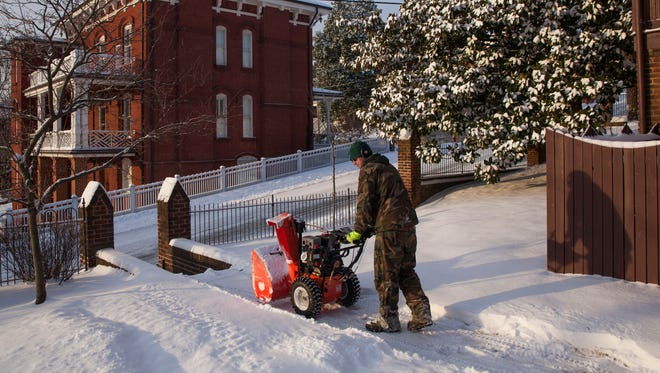 Derrick Simmons walks a snow blower along a brick walkway at Trinity Episcopal Church in Staunton while working to clear the path on Tuesday, Feb. 17, 2015.