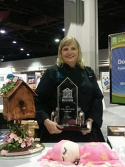 Donna Barley holds her first-place trophy next to one of her winning cakes at the IDDBA Cake Decorating Competition in Atlanta on June 9.