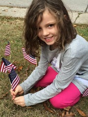 First-grader Brooke Fox places her flag in the ground at Forest Elementary School.