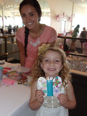 Hope's Closet volunteer Natalia Stromak helps Saylor Wells make a paper butterfly.