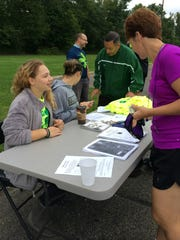 Audrey Bennett registers participants for the Fisher Catholic 5K on Sept. 13 at Forest Rose School in Lancaster. Bennett organized the first Fisher Catholic 5K to benefit the school's tuition assistance program and athletic department.