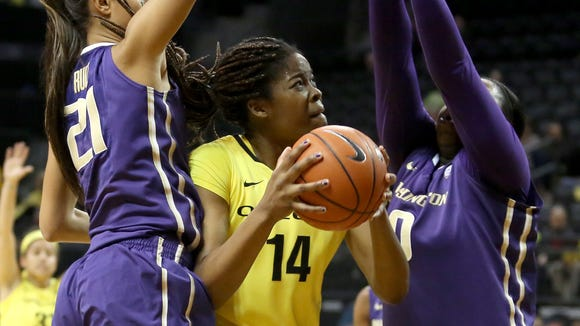 Oregon's Jillian Alleyne, center, under pressure from Washington's Brianna Ruiz (21) and Chantel Osahor during their game on Friday, Jan. 16, 2015, at the Matthew Knight Arena in Eugene, Ore.