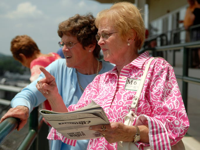 Sisters and cancer survivors, Mary O'Neill, left, and Jean Kittner, right, watch the first race at Churchill Down's Cancer Survivor's Day.
