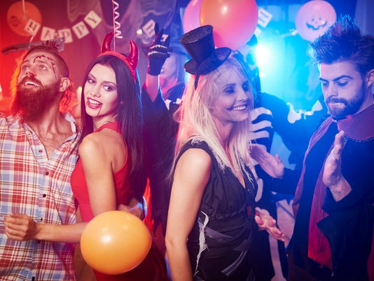Friends dancing at night halloween party