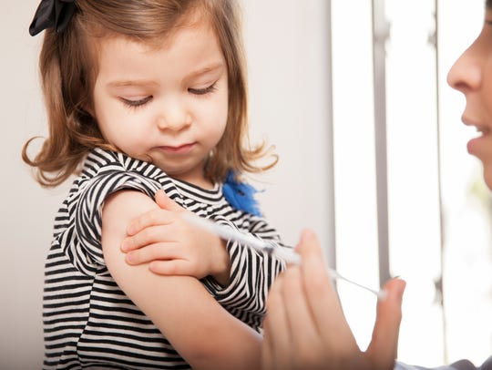 Little girl gets flu shot at a doctor's office.