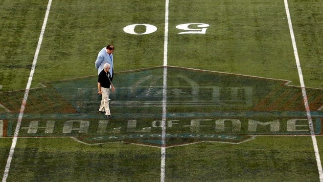 Pro Football Hall of Fame president David Baker, rear, inspects the conditions at midfield of Tom Benson Hall of Fame Stadium on Sunday night.