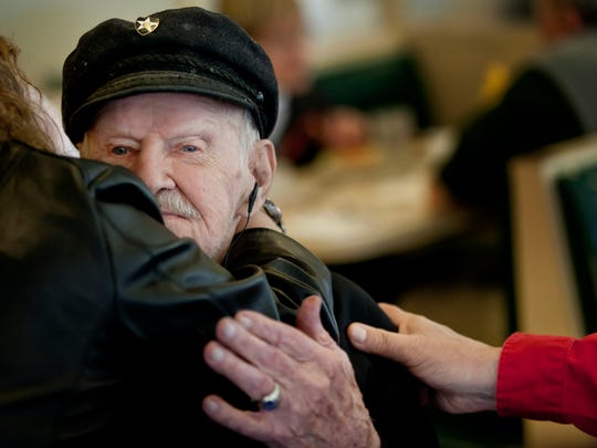 Carl Ladensack, a World War II veteran, gets hugs from friends and family during his surprise 99th birthday party Wednesday, May 6, 2015 at Tom Manis restaurant in Port Huron.
