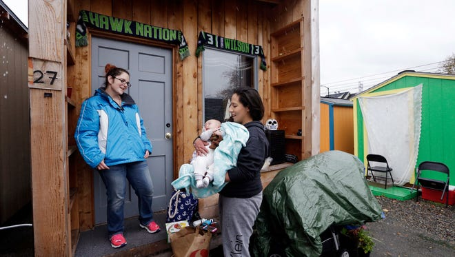 In this photo taken Thursday, Nov. 9, 2017, Eva Stough, right, holds her baby Kaysen Griffin, three months, as she returns to her tiny house where a neighbor greets her at a homeless encampment in Seattle. Tiny homes could be the solution to all kinds of housing needs, offering warmth and security for the homeless, an affordable option for expensive big cities and simplicity for people who want to declutter their lives. However, that seemingly broad support fails to translate into acceptance when tiny home developers try to build next door.