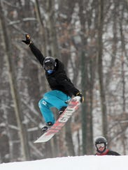 In this 2014 file photo, a snowboarder flies through