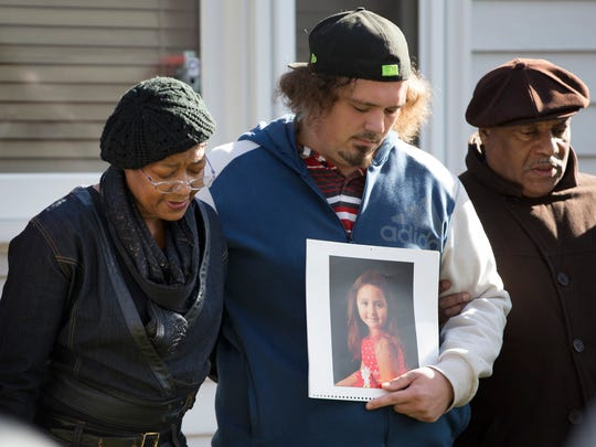 Robert Petersen (center) holds a photo of his slain 5-year-old daughter, Laylah, during a prayer circle where she was shot while sitting on her grandfather's lap by gunfire into the house.