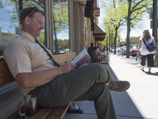 Andrew Bohn reads a book outside of The Bean Cycle
