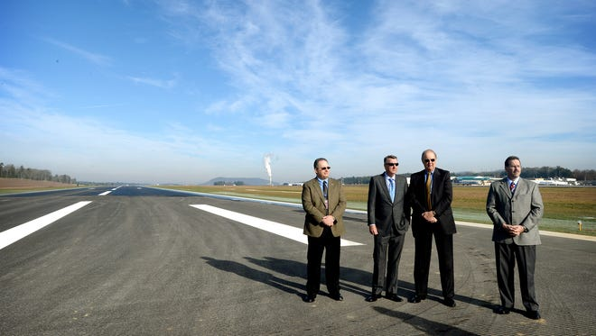 Officials with Asheville Regional Airport stand on a temporary runway shortly before it opened in December 2015. It was built to allow air service to continue while the airport's permanent runway is replaced.