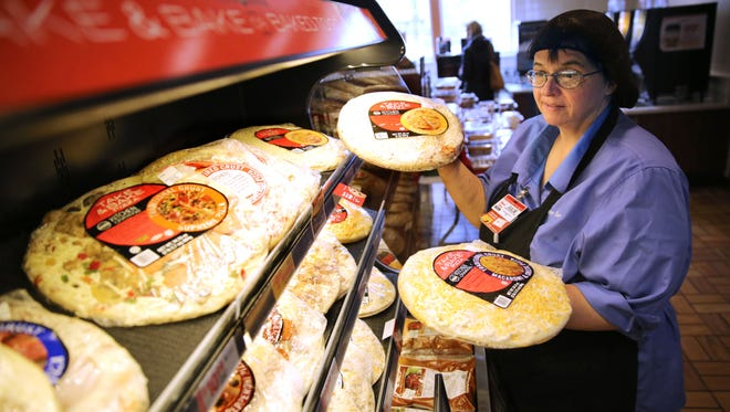 Julie Arntz, Kwik Trip assistant food service leader, looks for a place to stock a take-and-bake pizza at the Kwik Trip on Main Street in Menomonee Falls.