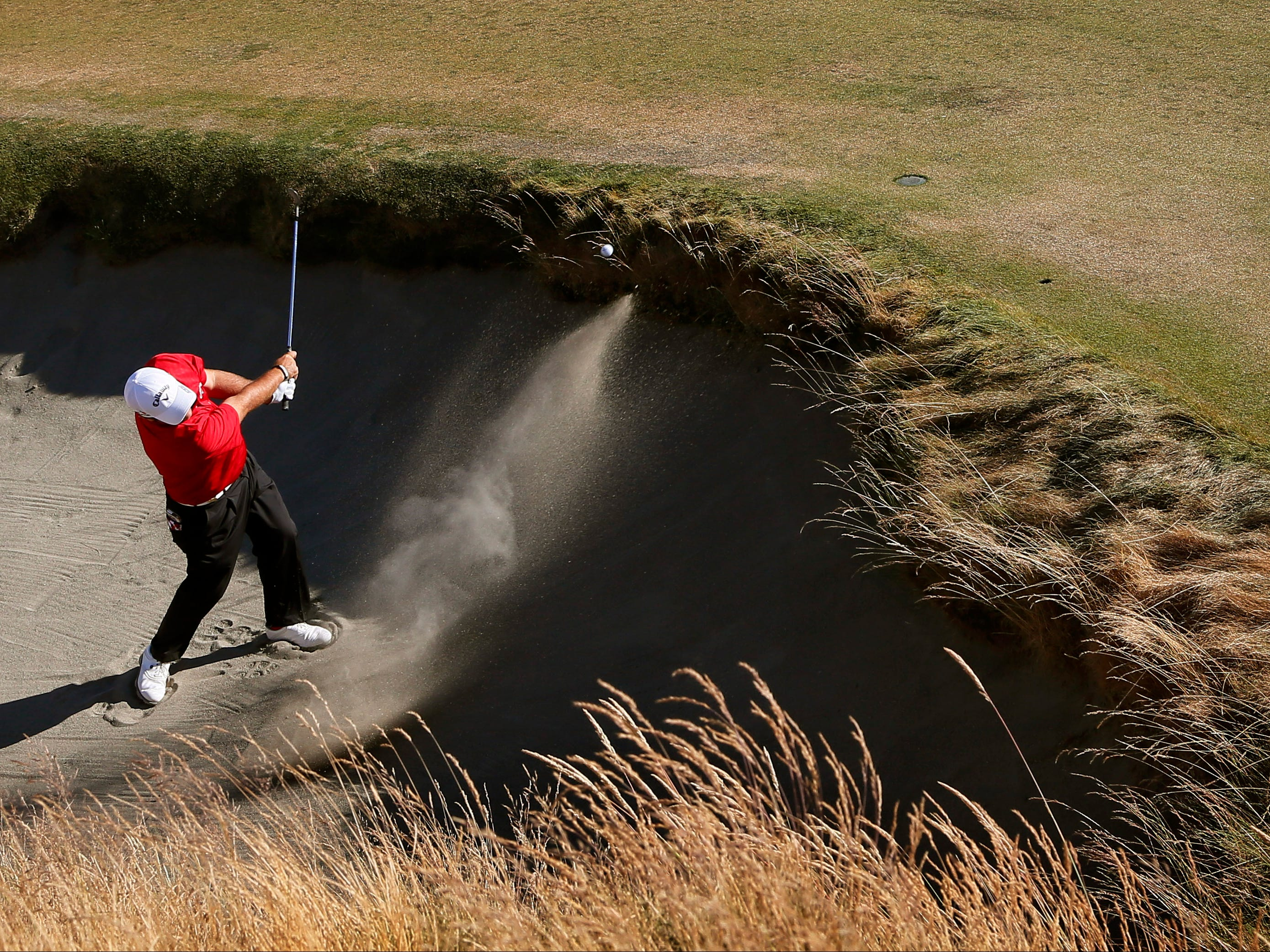 Patrick Reed hits out of the bunker on the 10th hole during the second round of the U.S. Open golf tournament at Chambers Bay on Friday, June 19, 2015 in University Place, Wash. (AP Photo/Matt York)
