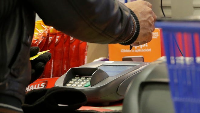 A man pays with a credit card while shopping at Kmart in New York.