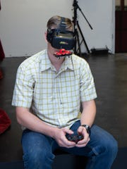 Bryndan Gardner pilots a mini drone while using a virtual headset to navigate at the Meet the Makerspace party on May 19, 2018.