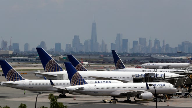 The New York skyline is seen in the background in this July 22, 2014, photo that shows United Airlines planes Newark Liberty International Airport.