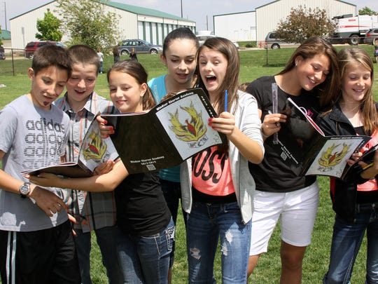From left, Micah Garcia, Ashton Dickson, Kenzie Rehor, Jessica Lindholm, Allie Carter, Alex Ramirez and Lilly Seilbach look at their yearbooks on the last day of school at Windsor Charter Academy.