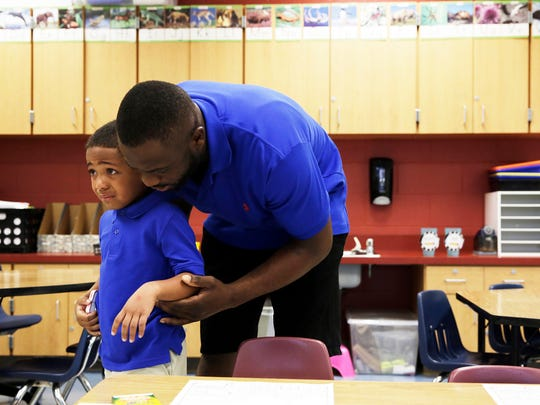 Fradel Zamor begins to cry as he says goodbye to his father, Fradel Zamor, for his first day of kindergarten at Highlands Elementary School in Immokalee on Monday, August 15, 2016.