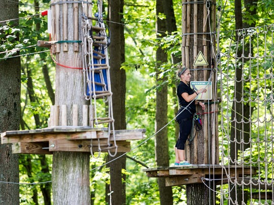 An employee closes up the Go Ape course for the day after a 59-year-old woman fell to her death at the zip line course in Lums Pond State Park on Wednesday, Aug. 24, 2016.