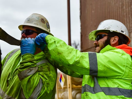EnviroCore Inc workers Jake Bradley (left) and Rian Lopez struggle to remove a long pipe from a groundwater well after it becomes stuck in the sediment. The well is one of several located in and around the former Fairfield Engineering property, 324 Barnhart St..