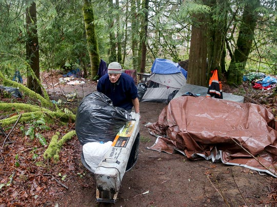 "A resident at a former homeless camp on Almira Drive in East Bremerton uses a wheelbarrow to help clean up an encampment before it was cleared in 2018. Kitsap County officials are looking for funding and a location to site a 75-bed ""Navigation Center."""