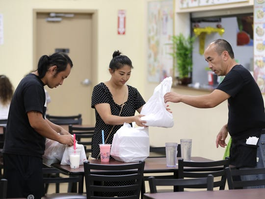 Ge Vang and his fiancee Mai Moua receive takeout from
