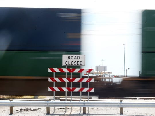 A freight train rolls past the closed Cadwallader Drive