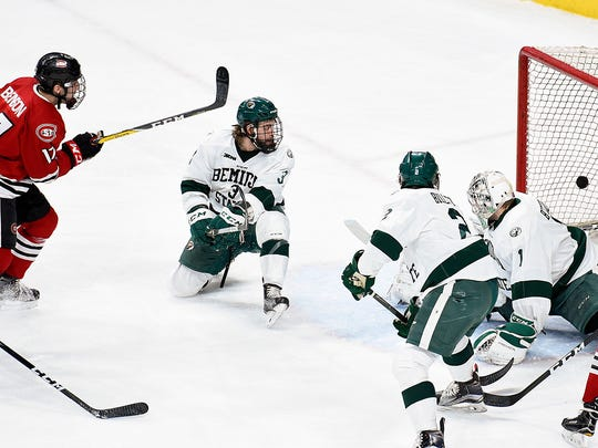 St. Cloud State's Jacob Benson puts the puck past Bemidji defenders and goalie Michael Bitzer to score in the first period Friday, Jan. 27, during the semifinals of North Star College Cup at the Xcel Energy Center.