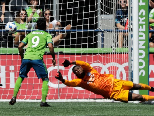 New York City goalkeeper Sean Johnson (right) can't stop a shot by Seattle Sounders midfielder Cristian Roldan as the Sounders' Raul Ruidiaz (9) stands poised for a possible rebound.