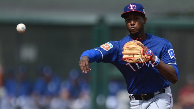 Texas Rangers second baseman Jurickson Profar (19) throws to first base during the first inning against the Kansas City Royals at Surprise Stadium.