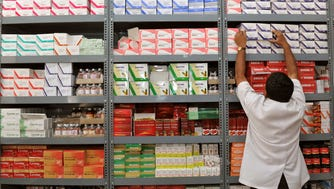 In this photograph taken on June 28, 2012, an Indian pharmacist pulls out a box of medicines from a shelf at a generic drug store at the Victoria Hospital in Bangalore.
