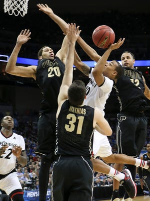 Cincinnati guard Troy Caupain, center, shoots between Purdue center A.J. Hammons (20), guard Dakota Mathias (31) and forward Vince Edwards during the second half of an NCAA tournament second round college basketball game in Louisville, Ky., Thursday, March 19, 2015. Cincinnati won 66-65 in overtime. (AP Photo/David Stephenson)