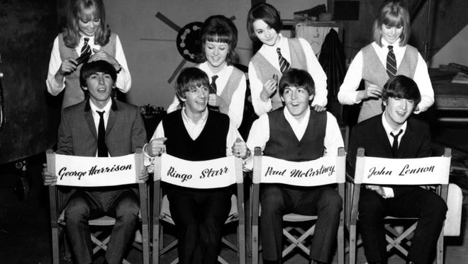 """The Beatles, George Harrison, Ringo Starr, Paul McCartney and John Lennon, have their hair combed by stylists on the set of their first movie production, """"A Hard Day's Night,"""" at Twickenham Film Studios in Middlesex, outside London, England, on March 12, 1964."""