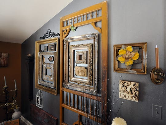 In the bedroom of her Mequon home, Gail Buenger painted one wall metallic pewter and three walls tobacco and then added an antique door and a collection of frames on one wall.