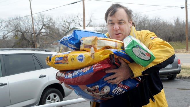 Dr. Keith Robinson overloads himself with bags of dog food, which he is dropping off at the Taylor-Jones Humane Society.