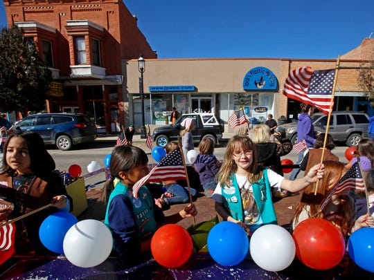 Girl Scouts hand out candy and hold up American flags on Saturday during the Veterans Day parade on Main Avenue in Aztec.