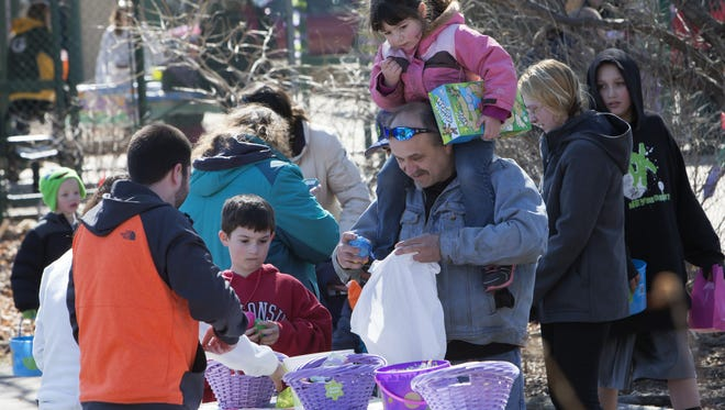 Families search for Easter eggs and rotate from station to station collecting prizes along the way, during last year's Egg-citing Day at the Zoo in Menominee Park. This year's event is Saturday, March 26.