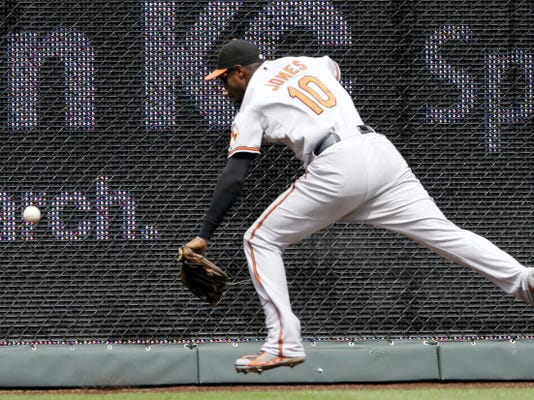 Baltimore Orioles center fielder Adam Jones chases a fly ball during the first inning of Thursday's game at Kauffman Stadium in Kansas City, Missouri. Jones was injured on the play but stayed in the game and Zobrist doubled.