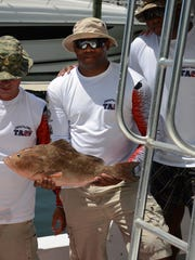 Air Force Sgt. Michael Walker holds onto a grouper he caught aboard Cuda. Headquartered at Hamilton Harbor Yacht Club for the first year, Take a Soldier Fishing returned to Naples to give 146 active duty servicemen and women the chance to enjoy a day of fishing, thanks to local captains.