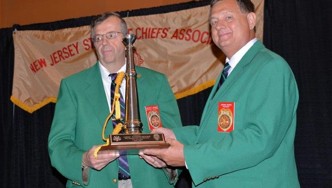 "Chris Assenheimer, (left) secretary of the New Jersey State Fire Chief's Association, presented Judson Moore, of Mauricetown, outgoing president, with a chief's bugle and plaque from the State Fire Chiefs Association at the Fireman's Convention in Wildwood.   The plaque read ""Presented to Chief Judson Moore, With Admiration on a Job Well Done, from your chiefs."" Incoming President William Newberry said that ""Chief Moore was one of the nicest gentleman he ever met. President Moore made a number of positive changes to our organization that was very beneficial."""