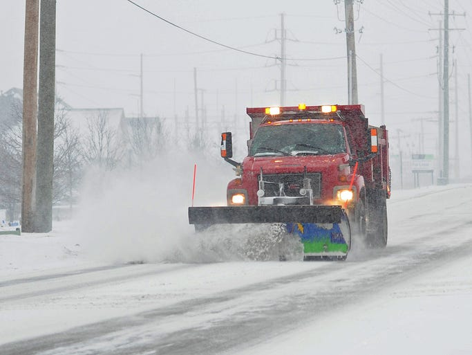 A snow plow travels on 116th Street, Tuesday, February 4, 2014, in Fishers.