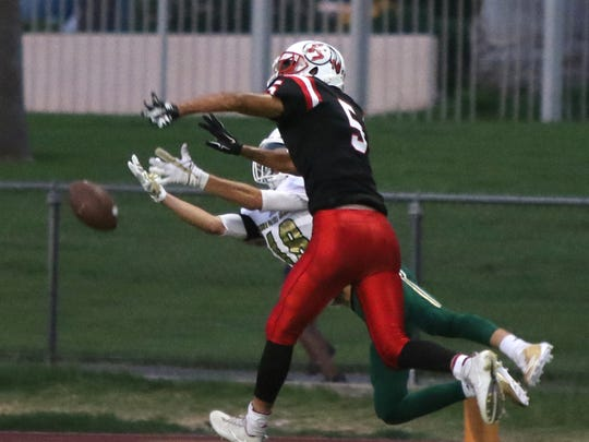 Palm Springs' Jadin Michaels defends against Murrieta Mesa's Cayden Chambers during the first half of their non-conference game in Palm Springs on Friday, September 8, 2017.