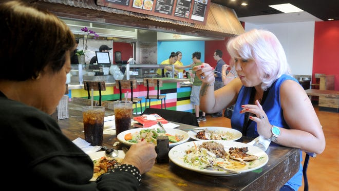 Tessie Godin, left, and Marie Galiguis, right, enjoy their food at the Caribbean Haven in Ventura. The restaurant combines Caribbean, Filipino and vegan fare. Owner is John Hutton. The food is all quite tasty in generous portions.