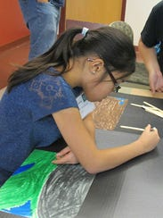 A student works on a scaled-up puzzle piece as part