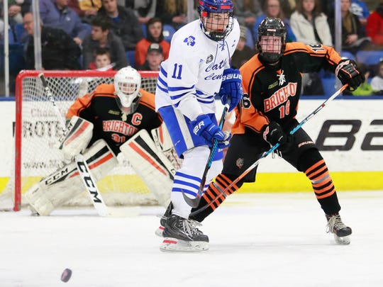 Brighton defenseman Brody White (right) defends against Detroit Catholic Central's Zach Sprys-Tellner in front of goalie Logan Neaton.